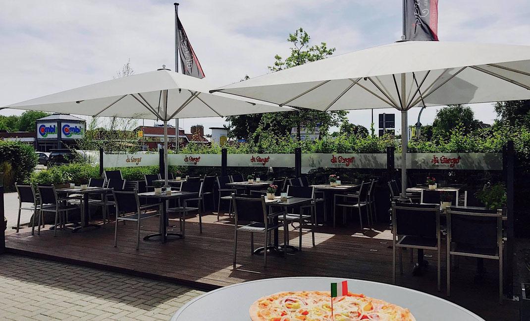 Terrasse mit Windschutz und Sonnenschirmen auf einem Holzpodest