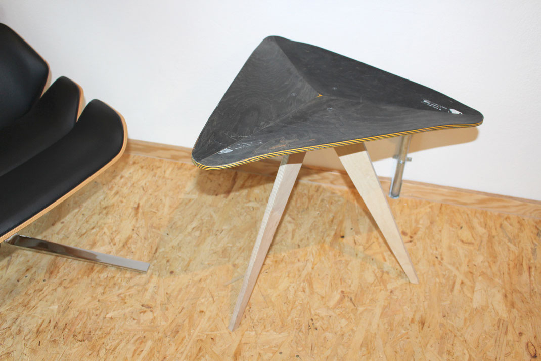 Tisch handgefertigt aus alten Skateboards. Loungechair mit einem kleinen Kafeetisch auf Holzboden. Loungechair with coffetable made from recycled skateboards. Dreieckiger Tisch mit schwarz gelben Holzschichten aus Ahorn. DesignMöbel aus recycling Material