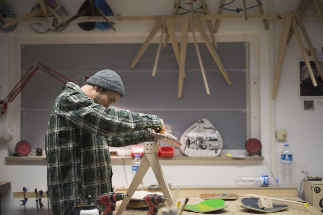Florian Bürkle in seiner Holzwerkstatt in welcher Möbel aus recycling Materialien handgefertigt werden. Akkuschrauber als Werkzeug zur Montage von Skateboard Möbeln.