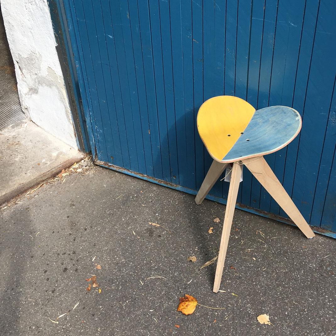 skateboard stuhl aus einem upcycling skateboard. ökologish wertvolle Design Holzarbeit. Herbststimmung eines Stuhls vor blauer Tür.