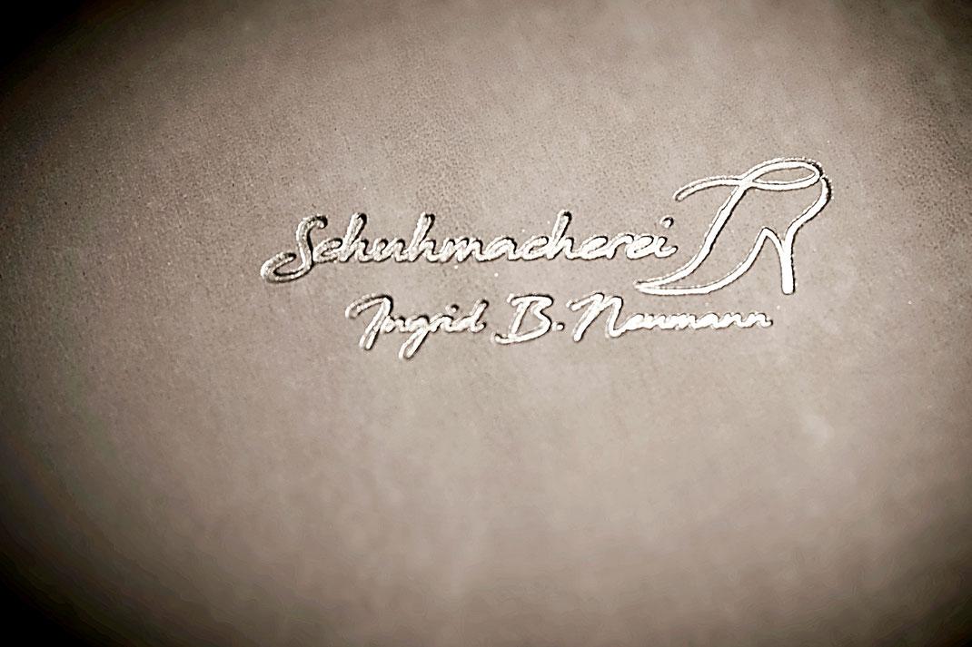 Schuhmacherei Logo auf Kalbsleder grau
