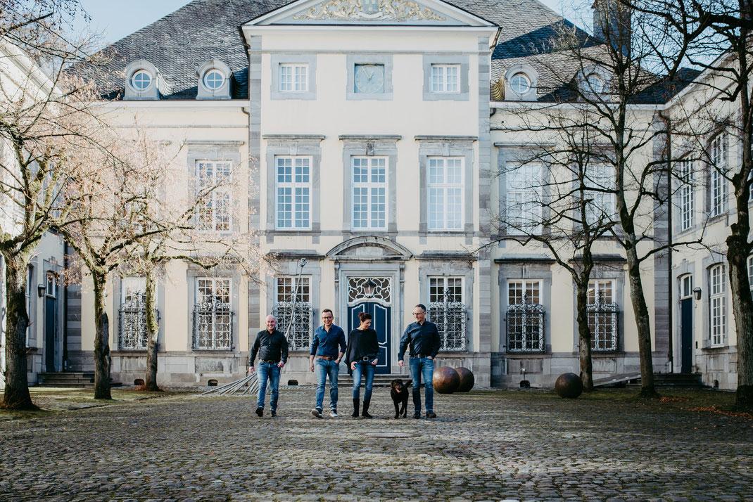 Patchworkfamilie mit Hund und zwei erwachsenen Jungs gehen vor dem Kunsthaus in Kornelimünster bei Aachen auf die Portraitfotografin Uschi Kitschke aus Kreuzau zu.