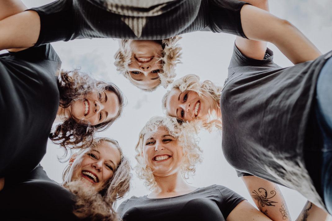 Fünf junge Frauen stehen im Kreis die Köpfe zusammen und schauen lachend nach unten in die Kamera fotografiert von Portraitfotografin Uschi Kitschke aus Kreuzau.