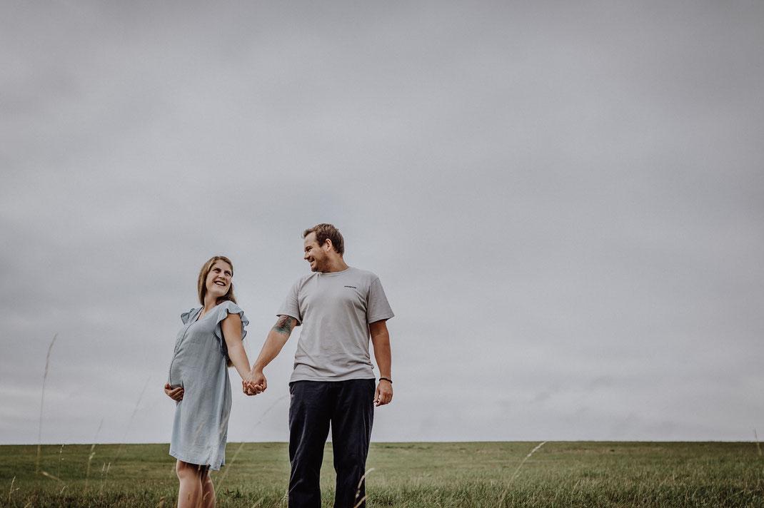 Junge werdende Eltern stehen Händchen haltend nebeneinander am Berg in Hürtgenwald und lachen sich an. Die werdende Mami hält stolz ihren Babybauch mit der rechten Hand fotografiert von Portraitfotografin Uschi Kitschke aus Kreuzau.