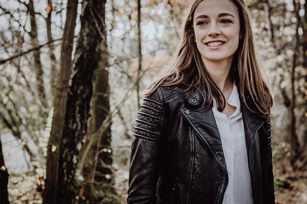 Portraitfoto von junger Frau in schwarzer Lederjacke draußen im Wald von Portraitfotografin Uschi Kitschke aus Kreuzau.