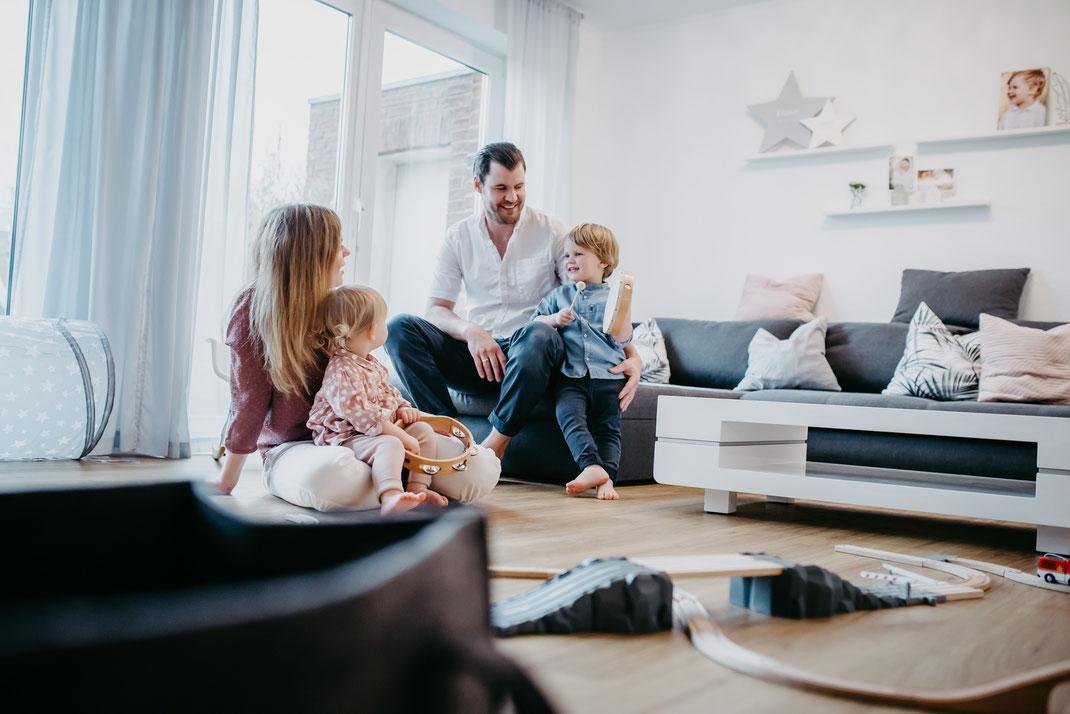 Junge Eltern sitzen mit ihrem kleinen Sohn und kleiner Tochter im Wohnzimmer und machen Musik. Eine Spielzeugeisenbahn steht im Vordergrund und die Kinder haben eine Rassel und eine Trommel in der Hand. Fotografiert von Uschi Kitschke aus Kreuzau.