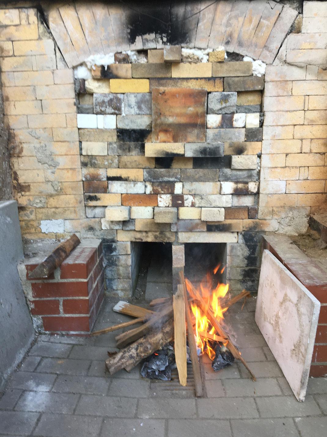 Kleines Anfangsfeuer vor dem Ofen