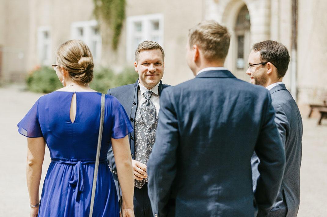 Bräutigam mit Hochzeitsgesellschaft im Schlosshof vor dem Schloss Wolkenburg