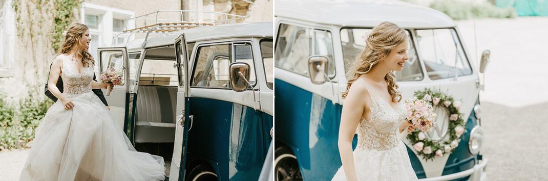 Braut mit Blumenstrauß vor dem Hochzeitsauto einem VW Bulli