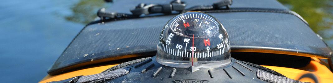 Bild von einem Kajak mit Peilkompass. Die Nadel zeigt 30 Grad an. Die Symbolik des Bildes ist Orientierung