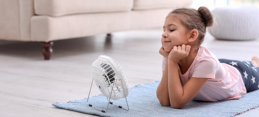 Mädchen liegt vor Ventilator auf dem Fußboden - Lüftung und Energiesparen