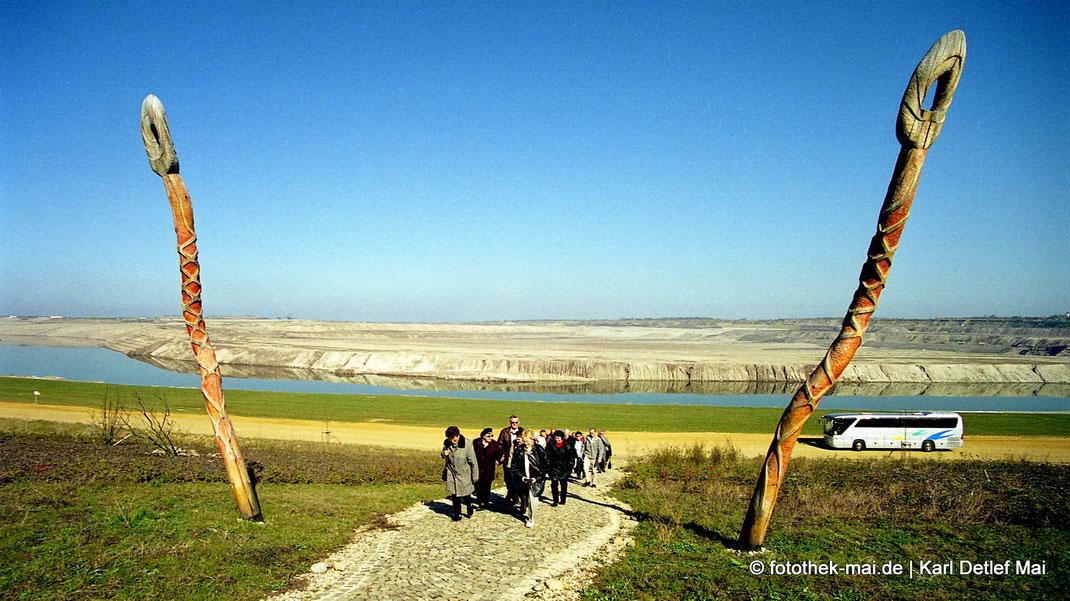 Teilnehmer Busexkursion im Kunstprojekt Butterfly zwischen zwei hölzernen Fühlern, im Hintergrund Bus am sich füllenden Störmthaler See