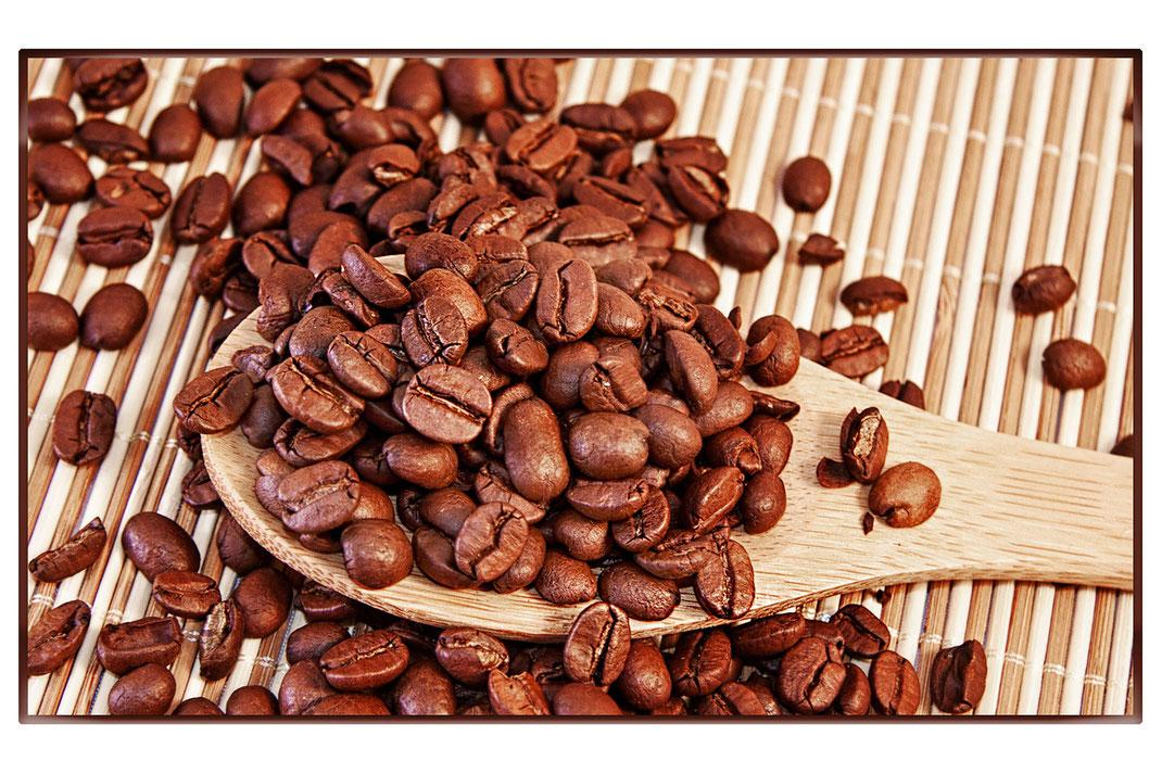 Geröstete Kaffeebohnen und  Holzlöffel liegen auf einer Bambusmatte