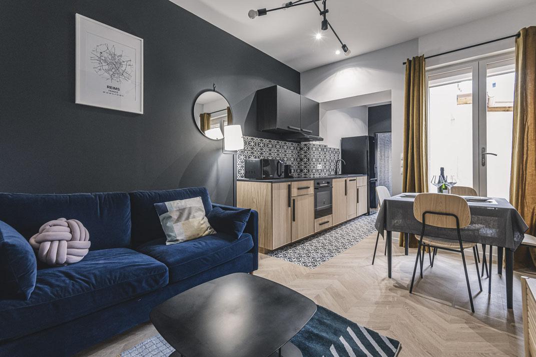 Décoration et aménagement airbnb, cuisine ouverte, mur noir, carreaux de ciment, canapé velours