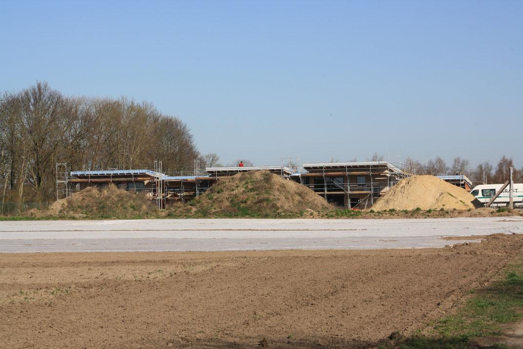 Hinter drei hoch aufgeschütteten Erdwällen ist eine Baustelle zu erkennen mit einem Neubau mit flachem Dach, der in ein Gerüst eingekleidet ist.