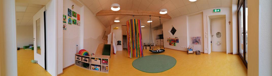 Blick in den Innenraum der Krippe mit gelbem Fußboden, Spielgeräten und Schaukel.