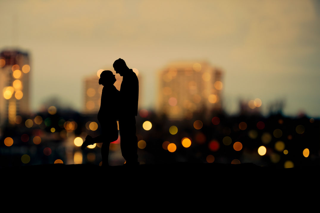 Male and female couple in silhouette in front of a bokeh city view. Buildings have an orange glow. Sky is blue. Couple is facing each other. Female has one leg kicked up behind her.