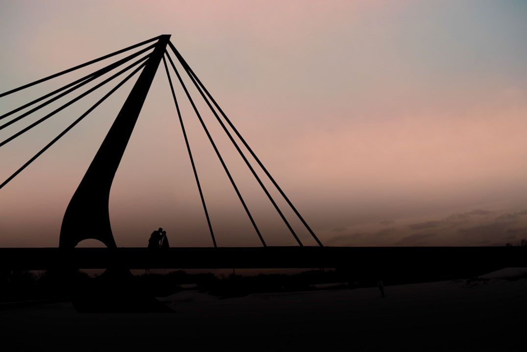 Bride and groom doing a dip kiss on a bridge at sunset. Couple is in silhouette. Bride is wearing a veil. Sky is pink and blue.