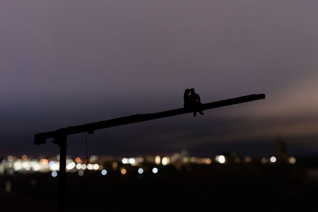 Male and female couple sitting on crane over city view at night. Couple is in silhouette.