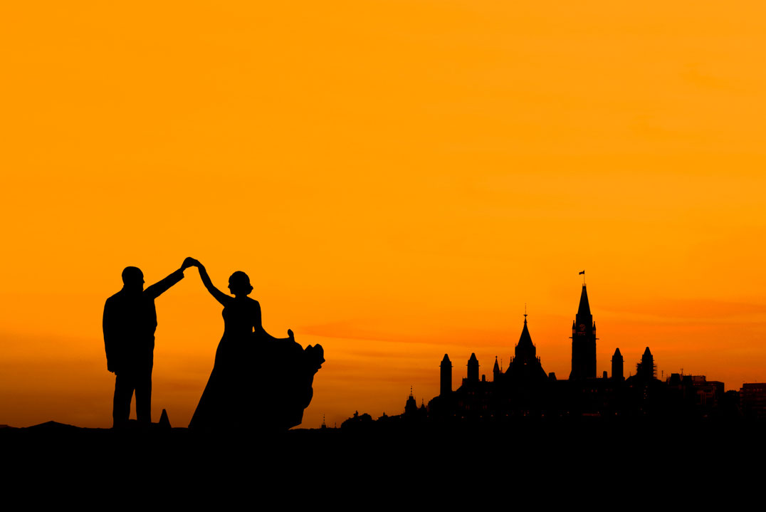 Photo of bride and groom in silhouette in front of Ottawa Parliament. Parliament hill is mostly in shadow. Sky is orange. Bride is wearing a dress and groom is wearing a suit. They are dancing.