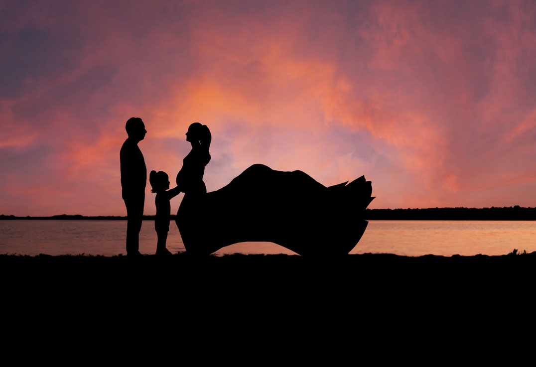 Family including one dad, one young girl, and one pregnant mom are in silhouette in front a beach at sunset. Girl is touching mom's belly. Dad is behind girl looking towards mom. Mom is touching her belly and wearing a maternity gown.