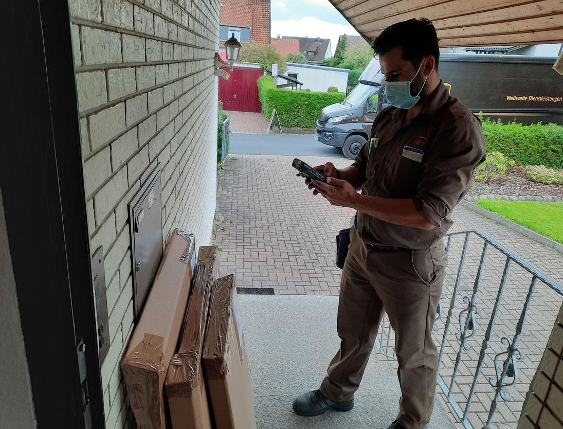 Der UPS Fahrer scannt dieBilder, die sich schon auf ihr neus Zuhause freuen