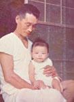 生後6ヶ月の頃。祖父に抱かれて。