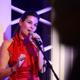 "Foto: ""Event Wedding Singer Anjes de Sangeres in rotem Kleid singend mit Microphone"""