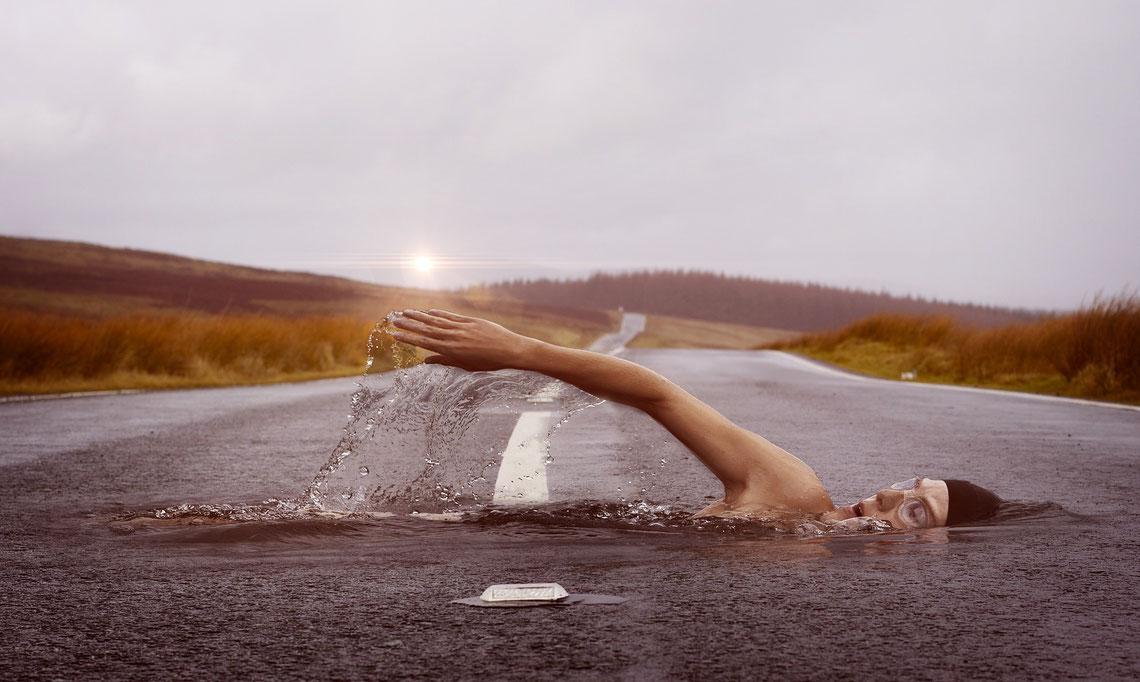 Ein surreales Bild bei dem ein Schwimmer durch eine Straße krault
