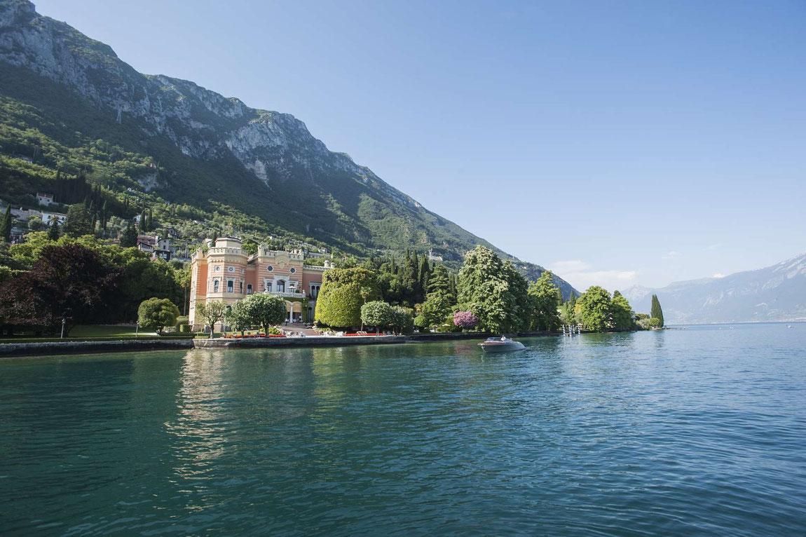 Villa Feltrinelli vom Gardasee aus aufgenommen mit Bergen im Hintergrund
