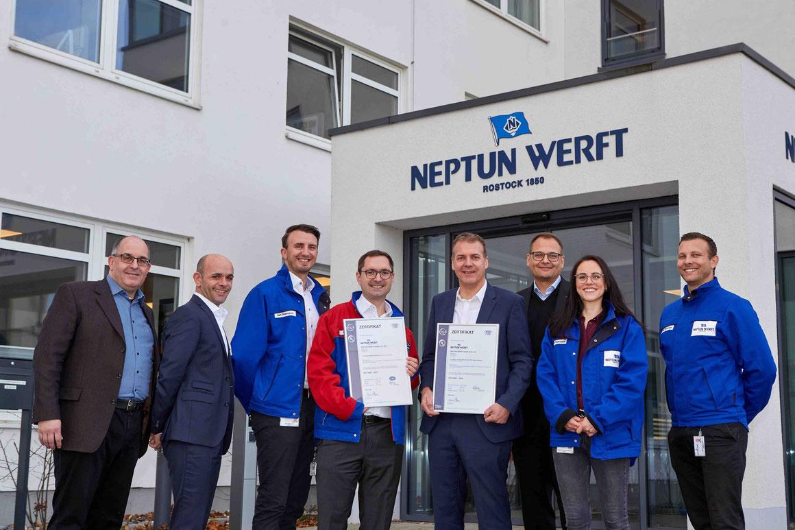 DQS-Geschäftsführer Markus Bleher (3.v.r.) überreichte Manfred Ossevorth, Geschäftsführer der NEPTUN WERFT, (4.v.r.) und Moritz Achilles, Abteilungsleiter Integriertes Managementsystem, (4.v.l.) die Zertifikate.