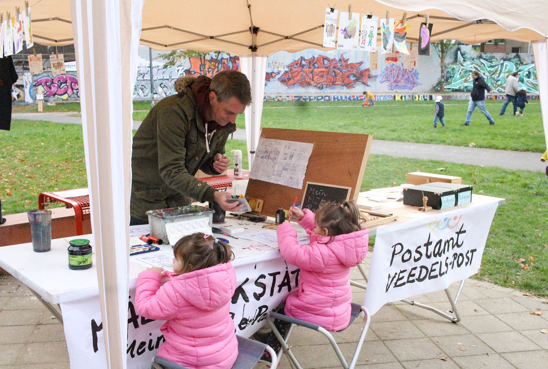 Malwerkstatt des STARKE VEEDEL BÜROs. Kinder malen auf vorgedruckten Postkarten. Im Postamt erhalten die Kinder Briefmarken und Stempel. Der Veedels-Briefkasten wird am Ende entleert. Ein T-Shirt wurde unter den jungen Künstler*innen verlost.