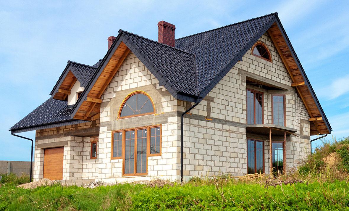 Unverputztes Einfamilienhaus mit Anthrazit gedecktem Dach.
