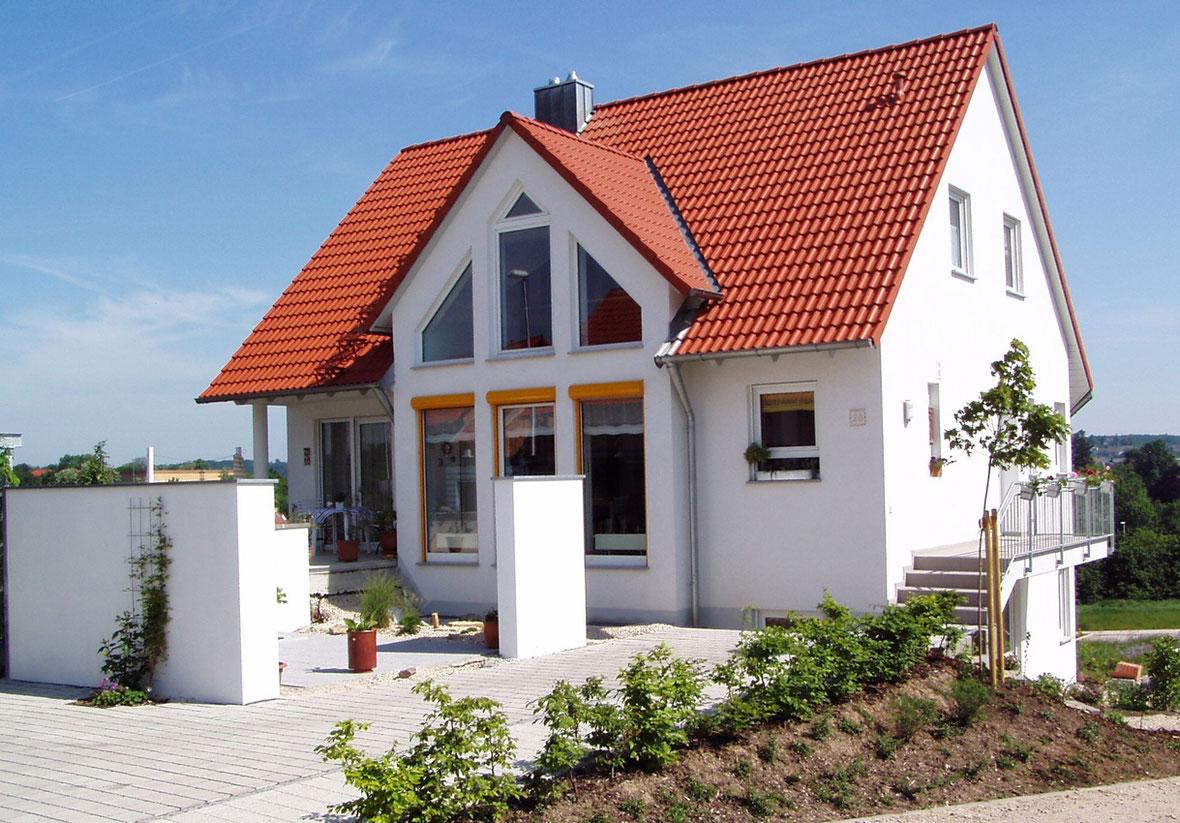 Einfamilienhaus mit eingedecktem roten Zigeldach.
