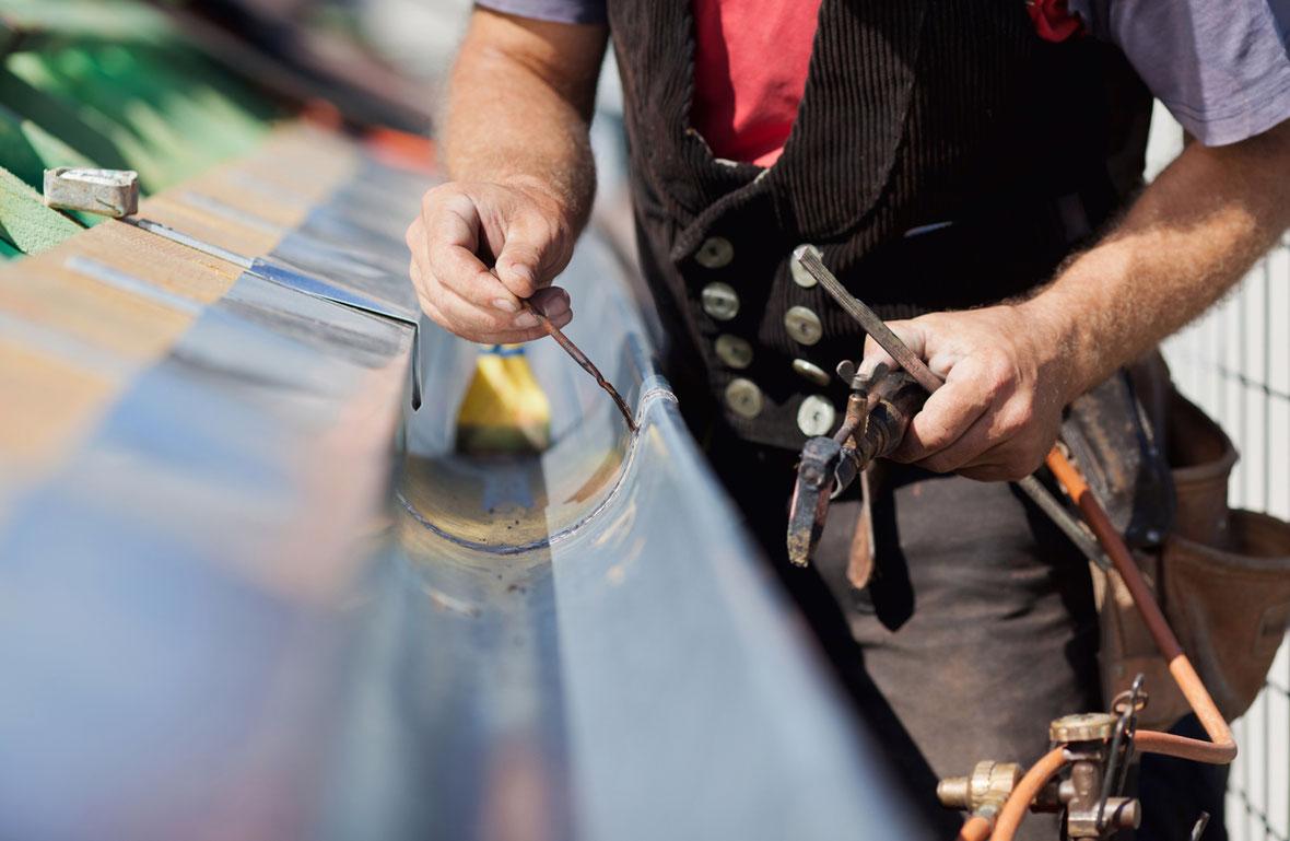 Spenglerarbeiten an einer Dachrinne.