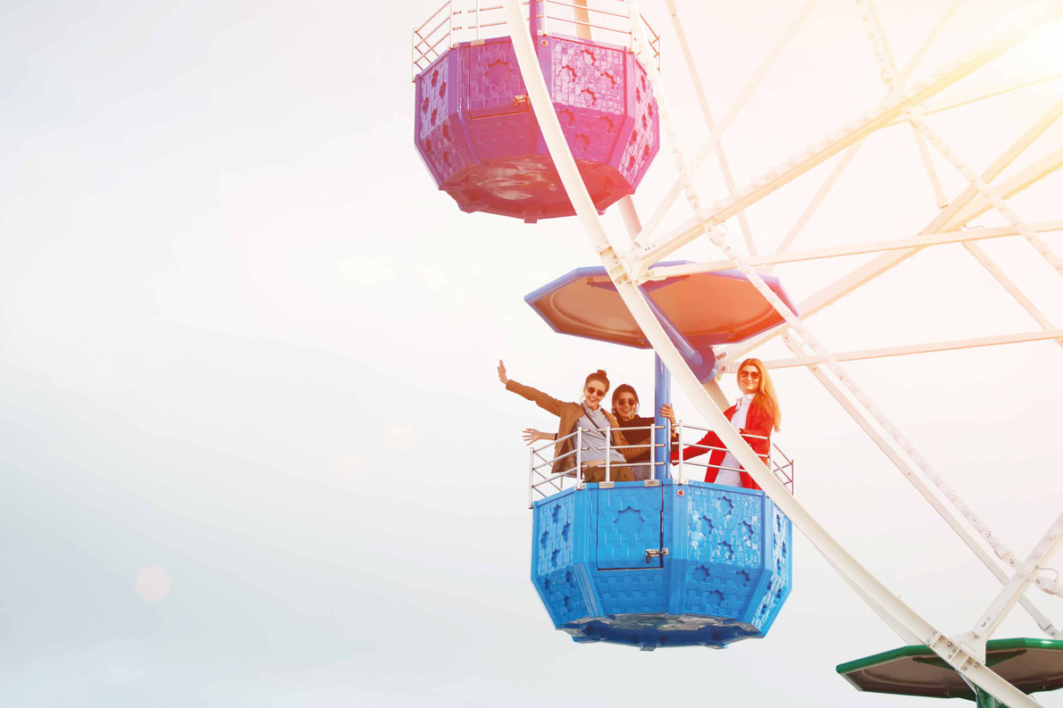 Most beautiful ferris wheels in Europe - Group of attractive young women having fun while they rotating on of colorful ferris wheel at sunny day Copyright GaudiLab