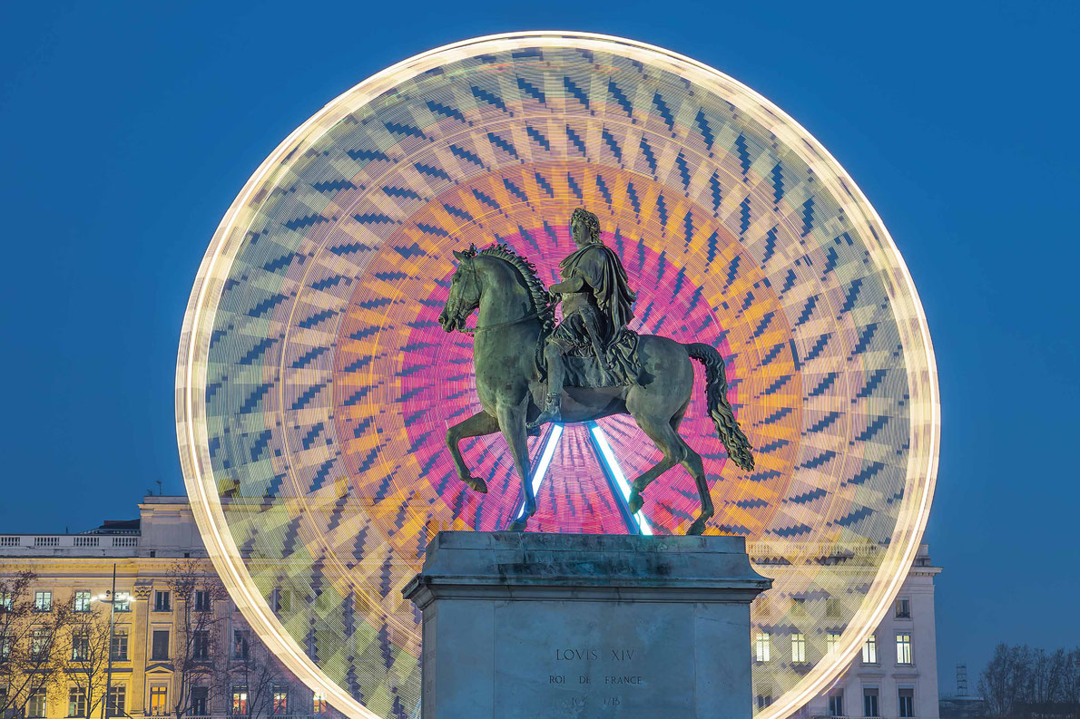 Most beautiful ferris wheels in Europe - Place Bellecour statue of King Louis XIV by night, Lyon France Copyright prochasson frederic