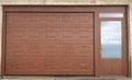 portoni sezionali finto legno scuro con porta laterale