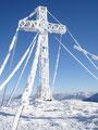 ... Gipfelkreuz mit strahlend blauem Himmel als Hintergrund.