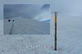 Das Rainertörl selbst markiert nur eine Holzstange mit einem Windspiel, welches schon von weitem zu hören war. Aufgrund des auflebenden  Windes gab der Hochnebel ein  kleines  Fenster frei, mit einem ersten Blick auf den Gipfelgrat.