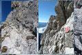 Anfänglich leitete der Klettersteig einige Meter bergab, dann auf der Südseite über eine versicherte Rampe (A) wiederum aufwärts und nach einem erneuten Abklettern (A/B) zum Steigbuch. Von hier über die 2. Schlüsselstelle (B/C), …