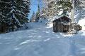 Die Last der Schneeschuhe vom Rücken genommen, ging es nun mit Schneetellern an den Füßen dem leicht ansteigenden Karrenweg zügig entlang. Dabei passierten wir zuerst eine kleine Wildfütterungsstelle, dann einen geöffneten Schranken und …