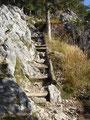 Über schroffes felsiges Gelände wo der Weg mit Holzstufen nach oben führt und im oberen Bereich teilweise ausgesetzt ist ...