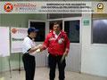 El Prof. José Moniz hace entrega del certificado e insignia metálica al C/2° (B) Headcliff Rodríguez, funcionario del Cuerpo de Bomberos del Estado Miranda.