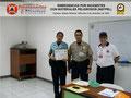 El Prof. Moniz y el Cmsrio. Bastardo hacen entrega del certificado e insignia metálica a la Sub-Inspectora Ana Moreno, adscrita a la Dirección Académica.