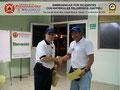 El Prof. José Moniz hace entrega del certificado e insignia metálica al C/1 ° (B) Víctor Mireles, funcionario del Cuerpo de Bomberos del Estado Miranda.