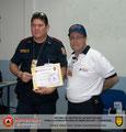 El Prof. José Moniz hace entrega del certificado e insignia metálica al Tte. (B) Rómulo Franco, Primer Comandante del Cuerpo de Bomberos de Carúpano.