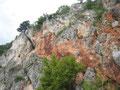 der Austriasteig quert nach links zwischem grauen und roten Gestein und endet nach der überdachten Rampe (links)