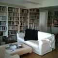 Großzügige Bücherwand, deckenhoch, teilweise mit Unterschränken.