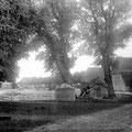 Hof Ganzow -  um 1920 | Blick vom Gutshaus zur Weizen- und Gerstenscheune, mittig: der mit Findlingen befestigte Teich, im Vordergrund: Holzmiete und landwirtschaftliches Gerät